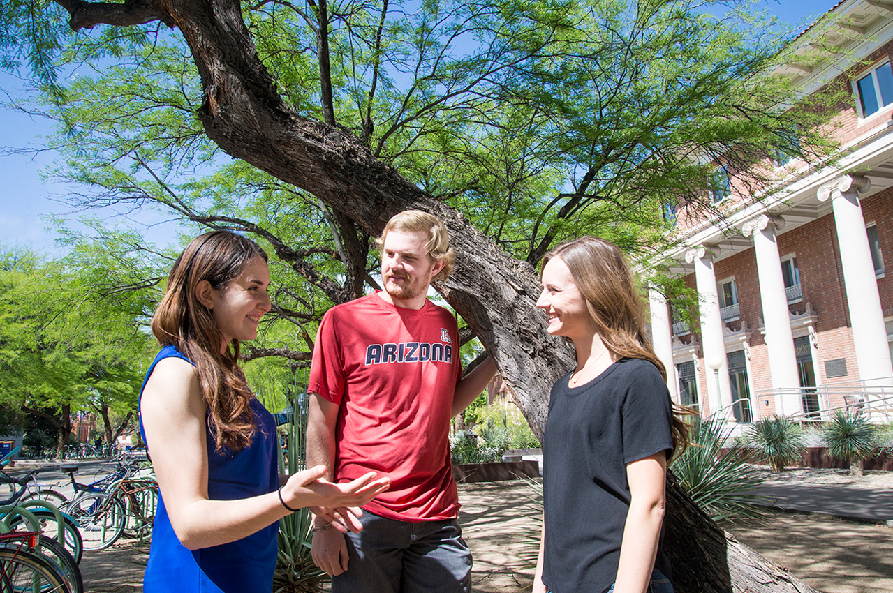 Three students converse on campus