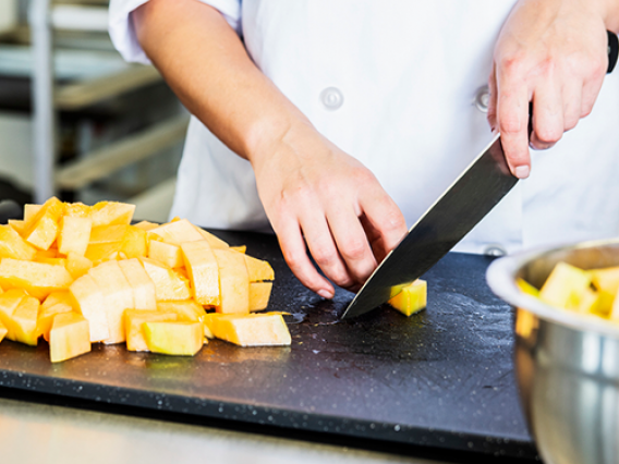Hands of person cutting pieces of cantaloupe
