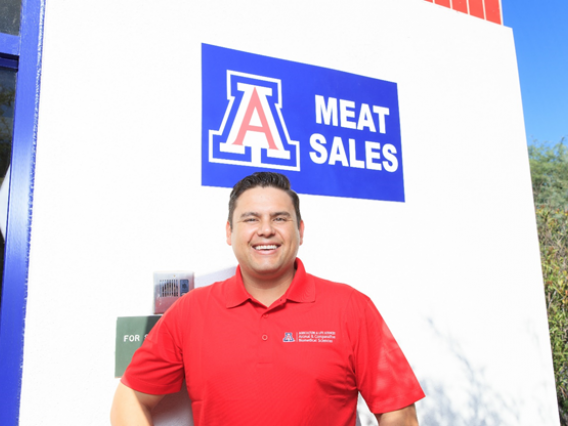 A man in a red shirt standing in front of a meat sales sign